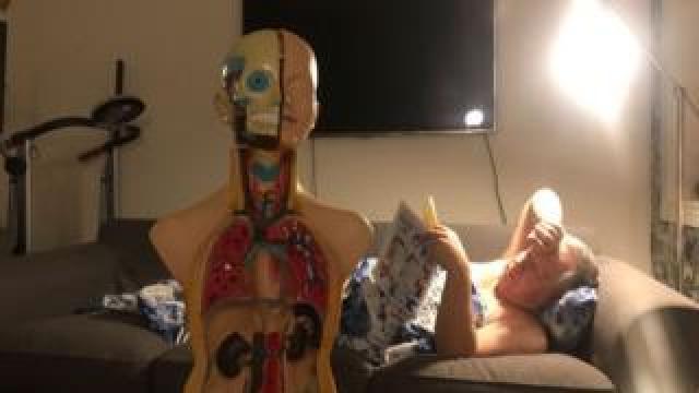Man sleeping in a loft with an anatomy doll