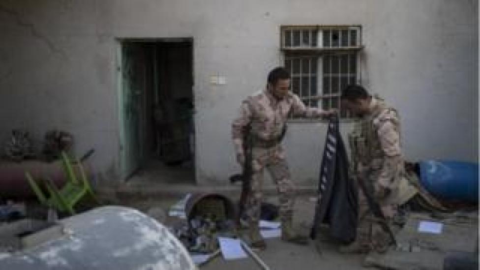 Kurdish Peshmerga soldiers look at a Islamic State flag inside an abandoned house in Faziliya, north of Mosul, Iraq, on 2 November