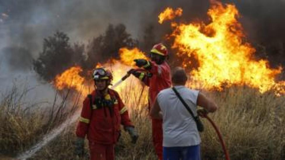 Firefighters and volunteers try to extinguish the fire broke out at forested land in Penteli town of Athens, Greece on July 23, 2018