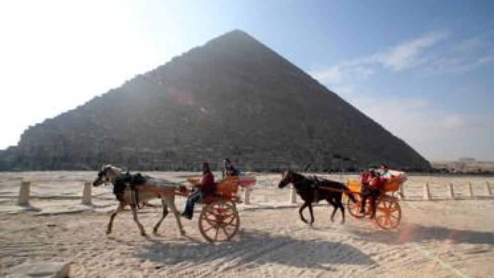 Image shows tourists in front of the Giza pyramids in Egypt