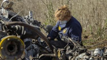 An investigator works at the scene of the helicopter crash that killed former NBA star Kobe Bryant