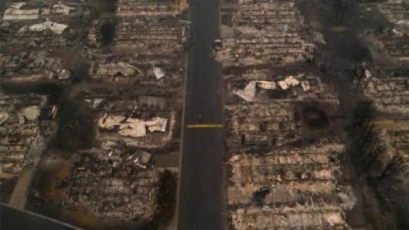 A person walks past gutted homes in the Medford Estates neighborhood in the aftermath of the Almeda fire