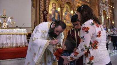 A child takes communion from a Roman Orthodox priest following the Sunday mass at the Saint Elias church Aleppo, Syria on May 10, 2020