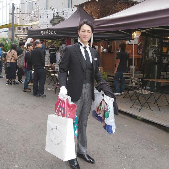 Yuichi Ishii vestido elegantemente de fraque e luvas brancas, carregando sacolas de compras
