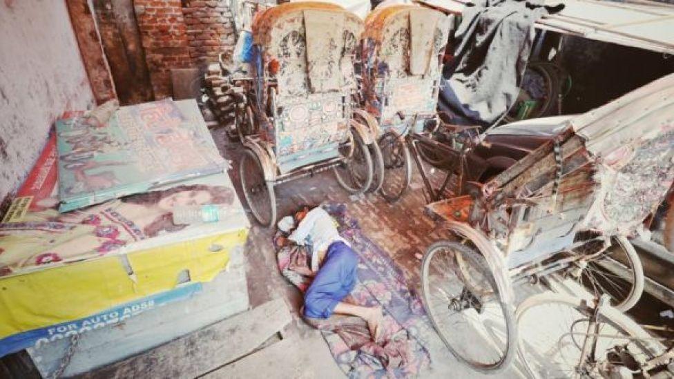 Kishan Lal lies next to his unused rickshaw