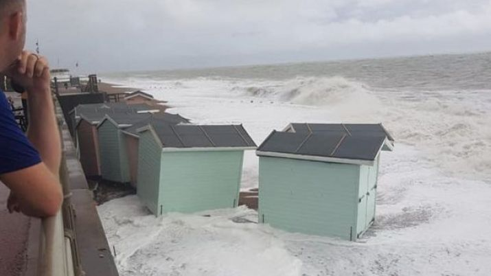 Beach huts lifted and washed down the beach by the waves