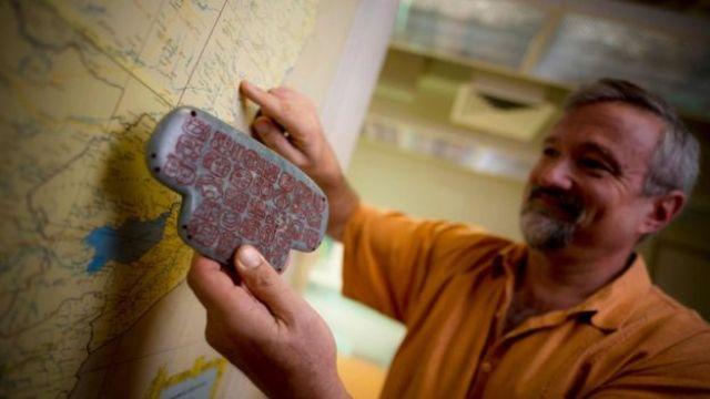 O arqueólogo Geoffrey Braswell, da Universidade da Califórnia, segura uma réplica do pingente