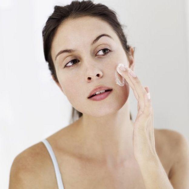 Una mujer echándose una crema