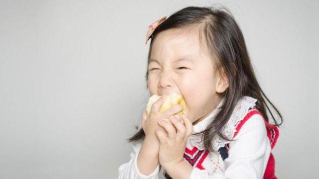Menina morde maçã