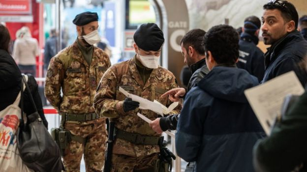 Italian authorities check passengers' documents at the Milan train station