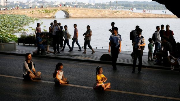 People pose, seated, for photos on an empty road near the West Lake, as police closed off many roads before G20 Summit in Hangzhou, Zhejiang Province, China. 31 August 2016.