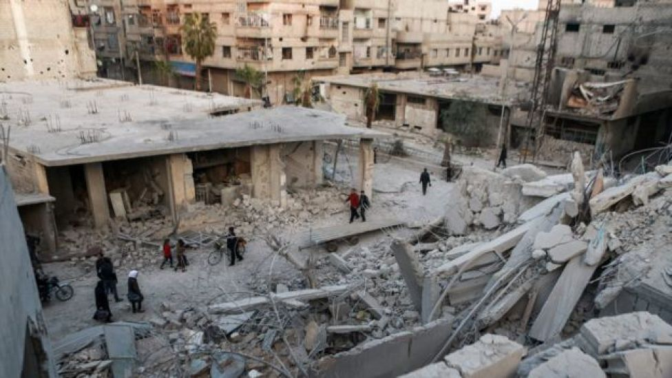 Syrians walk past destroyed buildings in Arbin, in the Eastern Ghouta outside Damascus, Syria (27 November 2017)
