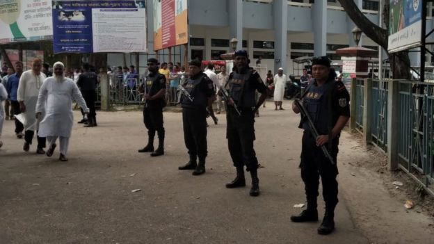 Police stand guard outside the court on 24 March