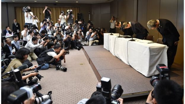 President of Toshiba, Hisao Tanaka (table centre), chairman Masashi Muromachi (table left) and corporate executive vice president Keizo Maeda (table right) bow at the beginning of a press conference at the company's headquarters in Tokyo on 21 July 2015.