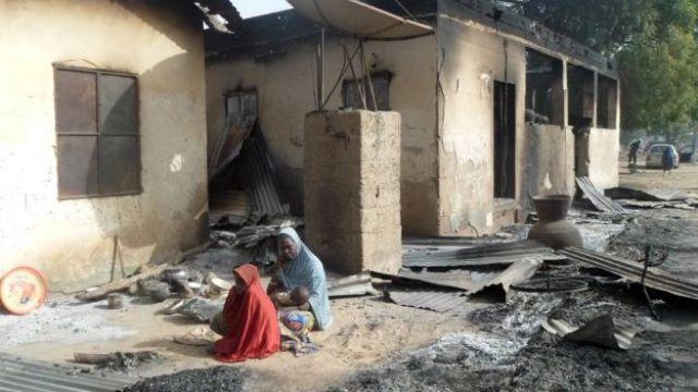 Dos habitantes de Nigeria frente a su vivienda quemada