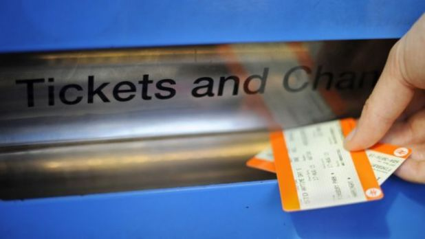 Person taking train tickets out of a ticket machine