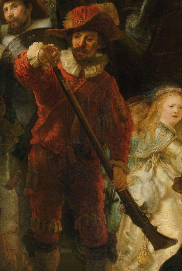 Mosquetero vestido de rojo con cuello y puños blancos, está cargando su mosquete con pólvora, y una joven vestida de dorado.
