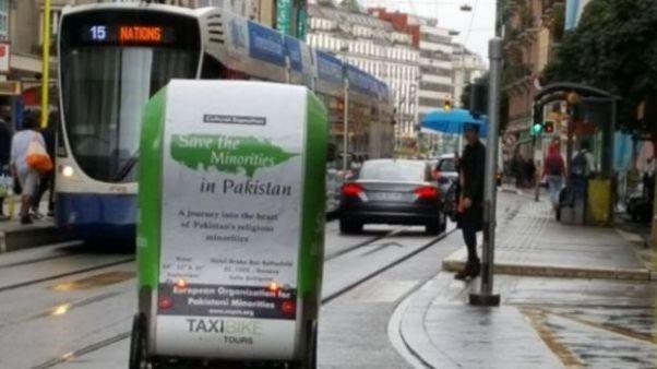 """Na rowerze taksówkowym w Genewie znajduje się plakat """"Ratuj mniejszości w Pakistanie"""""""