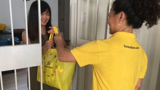 HonestBee delivery person handing over bag to customer