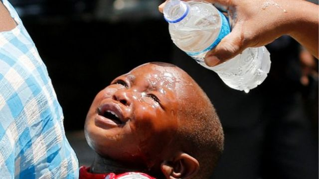 A woman pours water over a child affected by teargas after clashes between police and street vendors in central Harare, Zimbabwe, Tuesday 27 September 2016