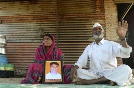 Una pareja dalit con la foto de su hijo muerto