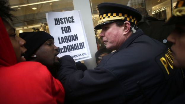 Police officers push back demonstrators who continue to protest the fatal police shooting of Laquan McDonald as they attempt to disrupt holiday shoppers along Michigan Avenue December 24, 2015 in Chicago, Illinois.