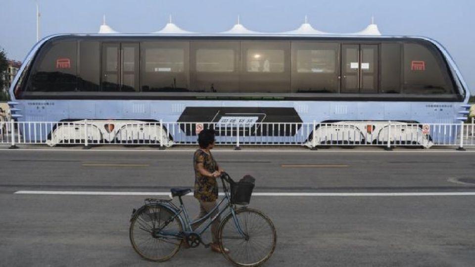 Una mujer maneja bicicleta mientras, al otro lado de la vía, circula el primer TEB en período de prueba
