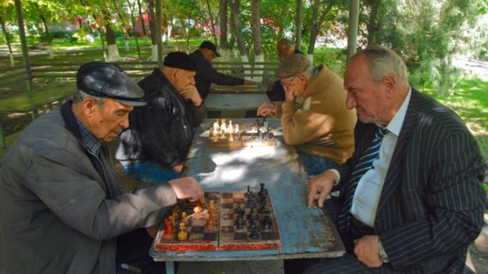 old men playing chess in the park