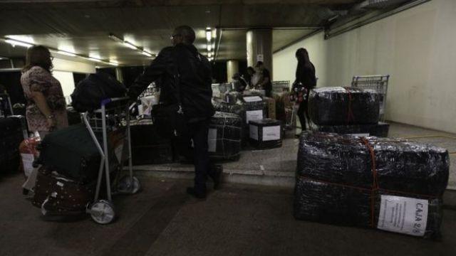 Médicos cubanos com malas e objetos embalados em aeroporto