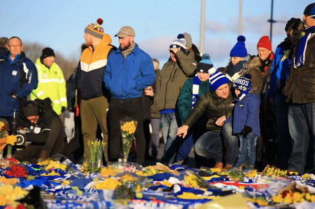 Fans place flowers and T-shirts with messages in tribute of Emiliano Sala before Cardiff's Premier League match against Bournemouth at the Cardiff City Stadium on Saturday