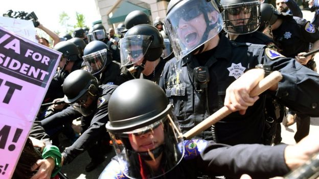 Police in riot gear hold back demonstrators against U.S. Republican presidential candidate Donald Trump outside the Hyatt hotel