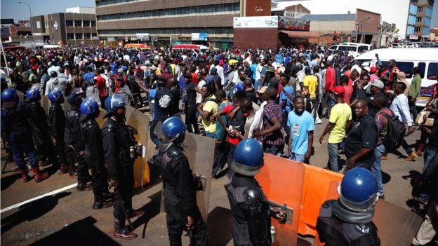 Wafuasi wa chama cha upinzani cha Movement for Democratic Change (MDC), chake Nelson Chamisa wakiimba na kucheza walipokuwa wakiandamana katika barabara za mji mkuu Harare, Agosti 1, 2018