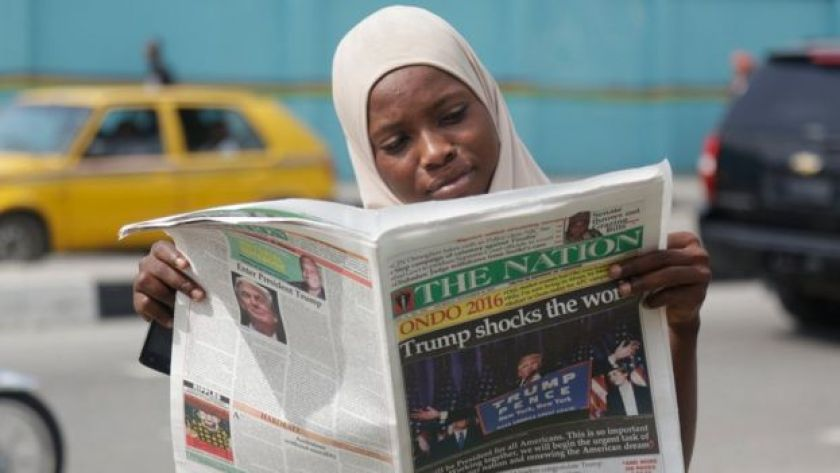 A Muslim woman reads a newspapers on a street in Lagos, Nigeria, reporting Trump's victory