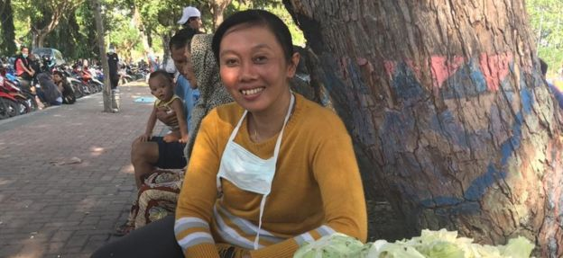 Erna Wahyuni smiles in front of a basket of cabbage