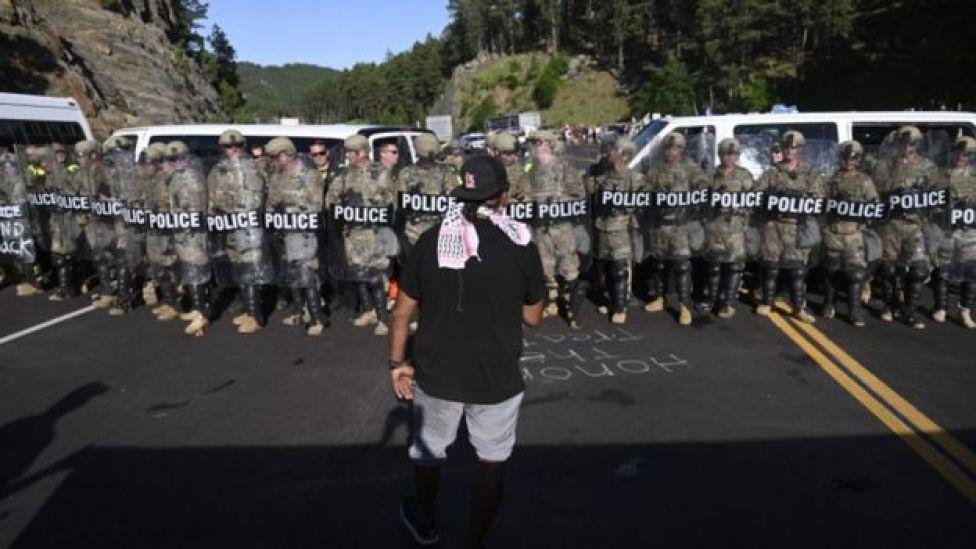 Un homme fait face à une rangée de policiers alors que des militants et des membres de différentes tribus de la région bloquent la route vers le monument national du mont Rushmore à Keystone, Dakota du Sud