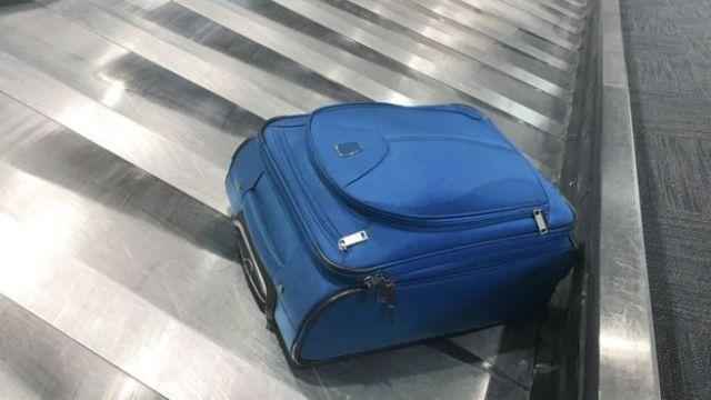 Mala azul na esteira do aeroporto