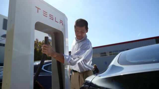 A man prepares to plug into a Tesla charging station in Fremont, California