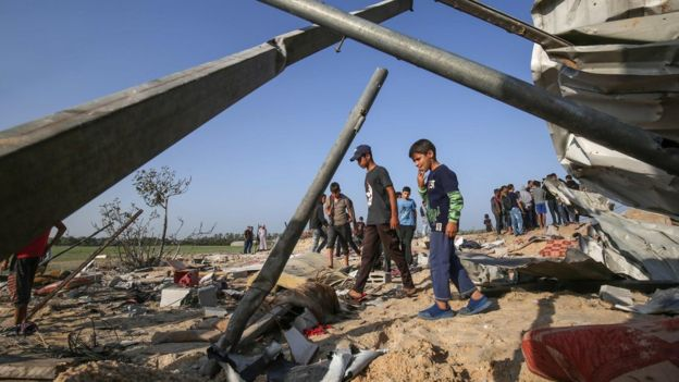 Palestinians inspect the remains of a building following an Israeli air strike in Deir al-Balah, in the southern Gaza Strip (14 November 2019)