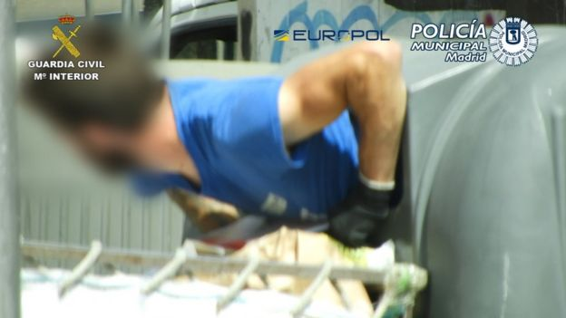 A man crawling out of a recycling bin in Madrid