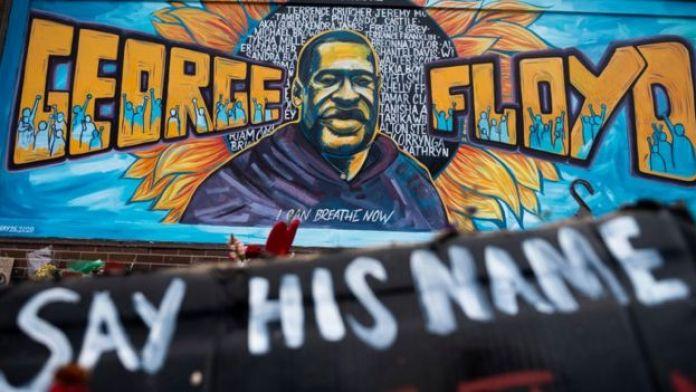 Un homme s'agenouille et lève son poing sur un site commémoratif