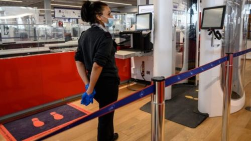 An airport staff member wearing protective face mask stands next to a body scanner in the boarding area of the Terminal 3 at Orly airport