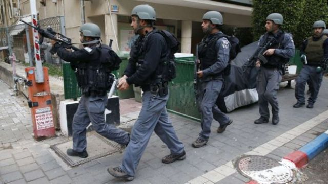 Members of the Israeli security forces patrol the area following an attack in Tel Aviv (1 January 2016)