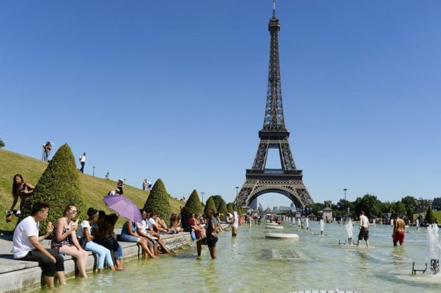 People refresh themselves in the water of the Trocadero fountains in front of the Eiffel tower in Paris, 19 July