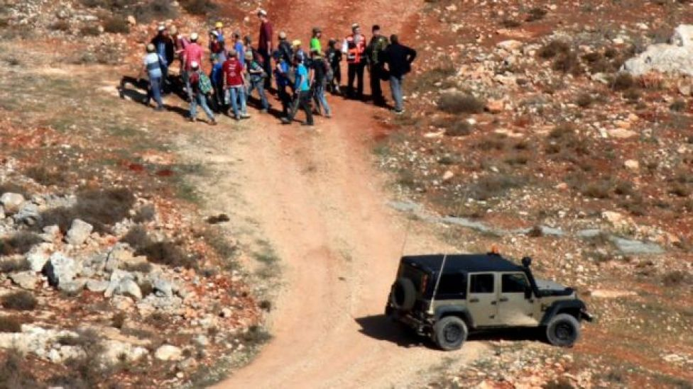 Israeli settlers are led away by Israeli soldiers after an incident near the West Bank village of Qusra (30 November 2017)