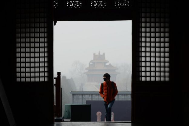 A man wearing a mask visits the Forbidden City in Beijing on 21 December 2016.