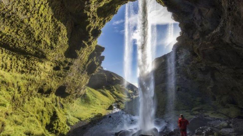 Mujer en una cueva en la que cae una catarata