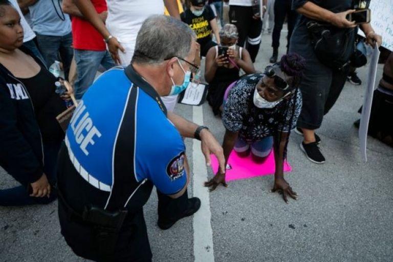 Un policía arrodillado junto a una manifestante