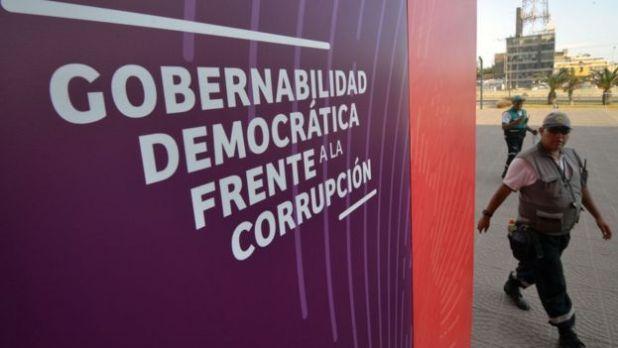 """Un funcionario pasa frente al cartel de """"Gobernabilidad democrática frente a la corrupción"""" para la Cumbre de las Américas en Lima, Perú."""