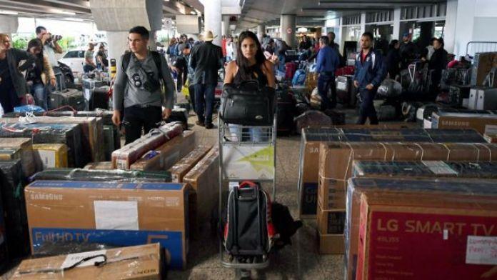 Em terminal, médicos cubanos carregam malas e pacotes de viagem