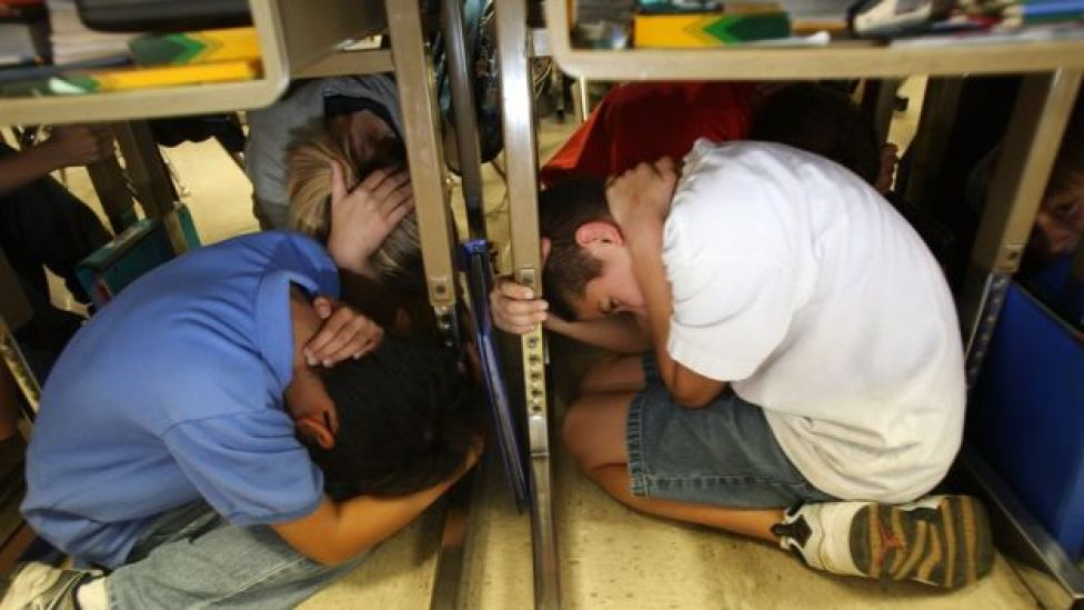 Niños se refugian bajo los escritorios en un ejercicio de preparación para terremotos